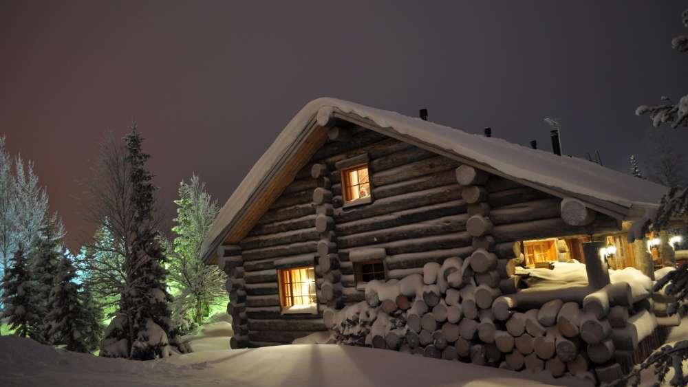 Snowy log cabin at night wallpaper