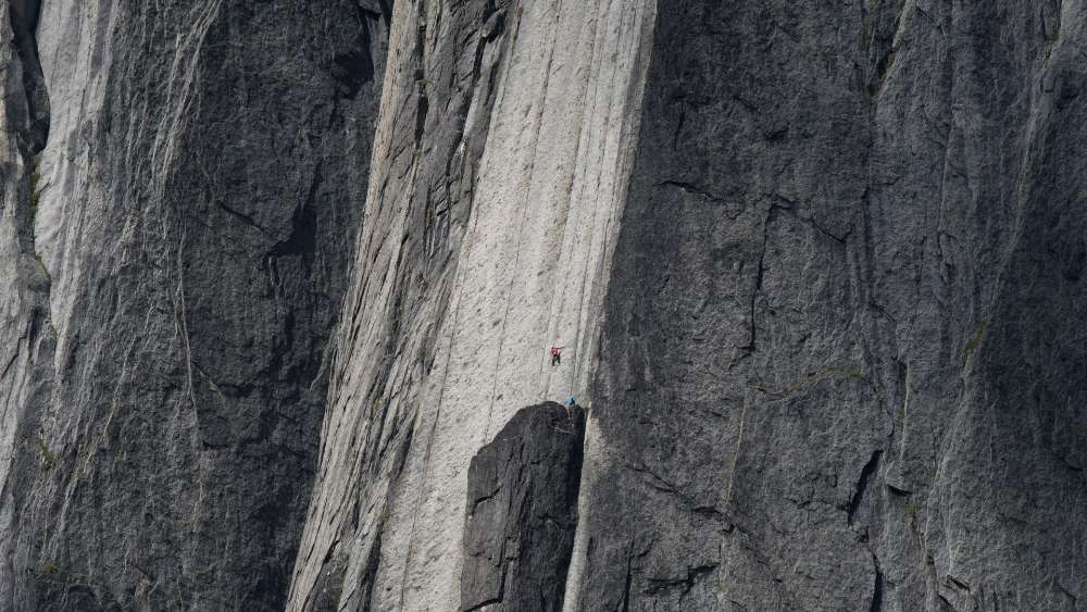 Huge cliff with a climber wallpaper
