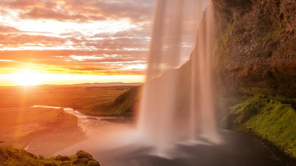 Behind the Seljalandsfoss waterfall at midnight sun wallpaper