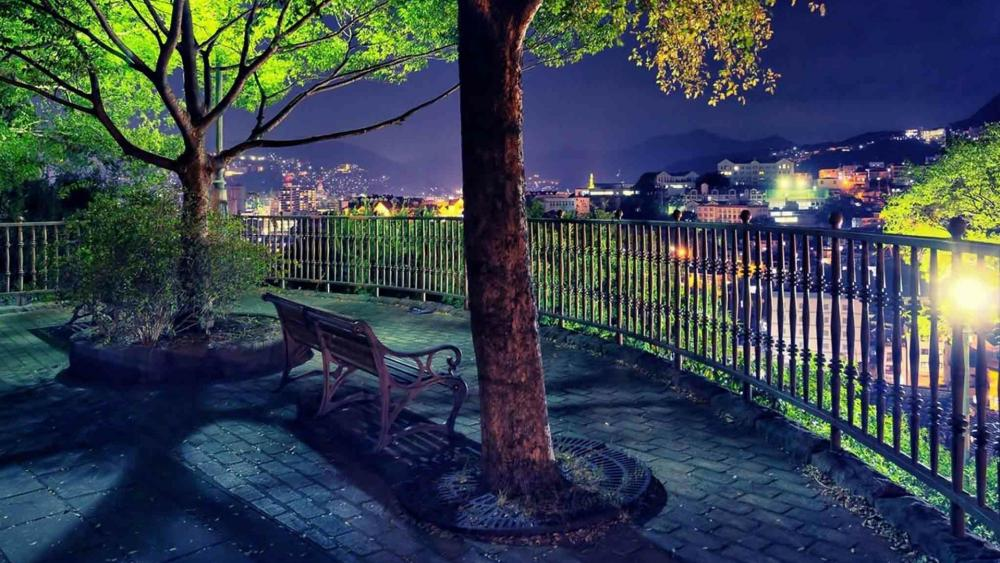 Lone bench over the lights of the city wallpaper