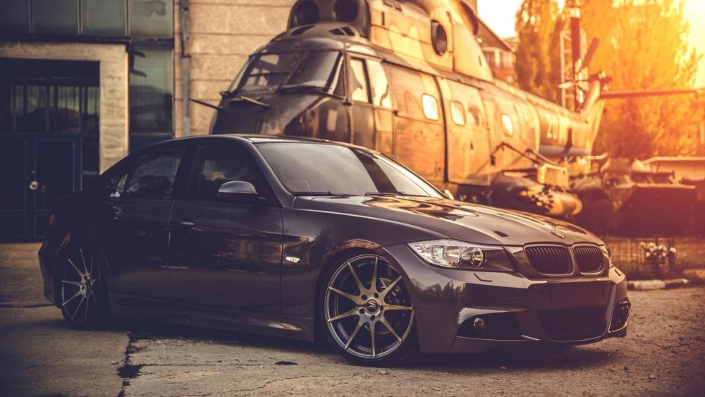 Black BMW E90 with a helicopter wallpaper