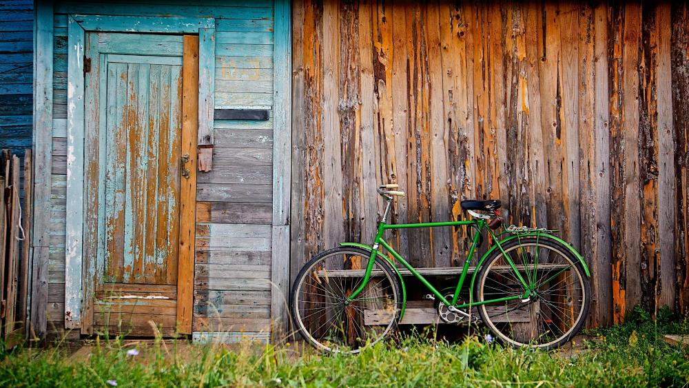 A green bicycle in front of a cabin wallpaper