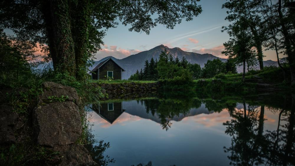 Wooden cottage reflected in a pond wallpaper