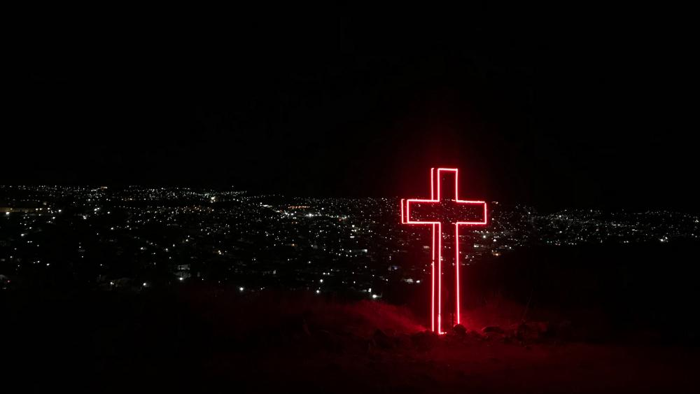 Red light cross above the city wallpaper