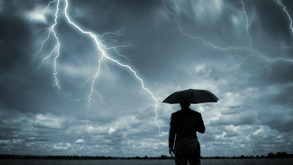 Man with umbrella in a storm wallpaper
