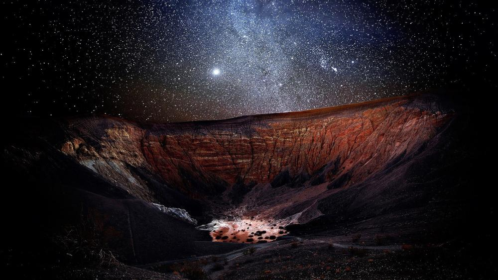 Starry night sky above a crater wallpaper