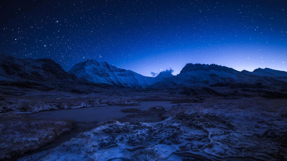 Starry night sky above the snowy mountains wallpaper