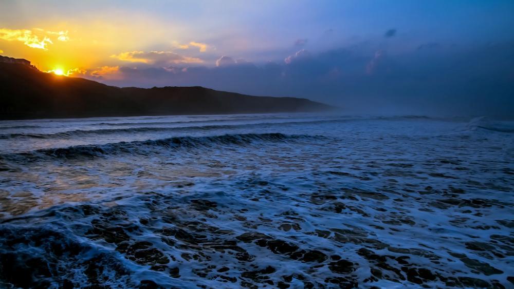 Foamy sea waves at sunset wallpaper