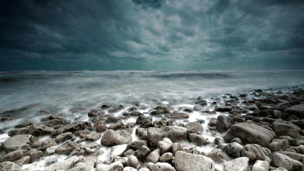 Stormy clouds above the stony beach wallpaper
