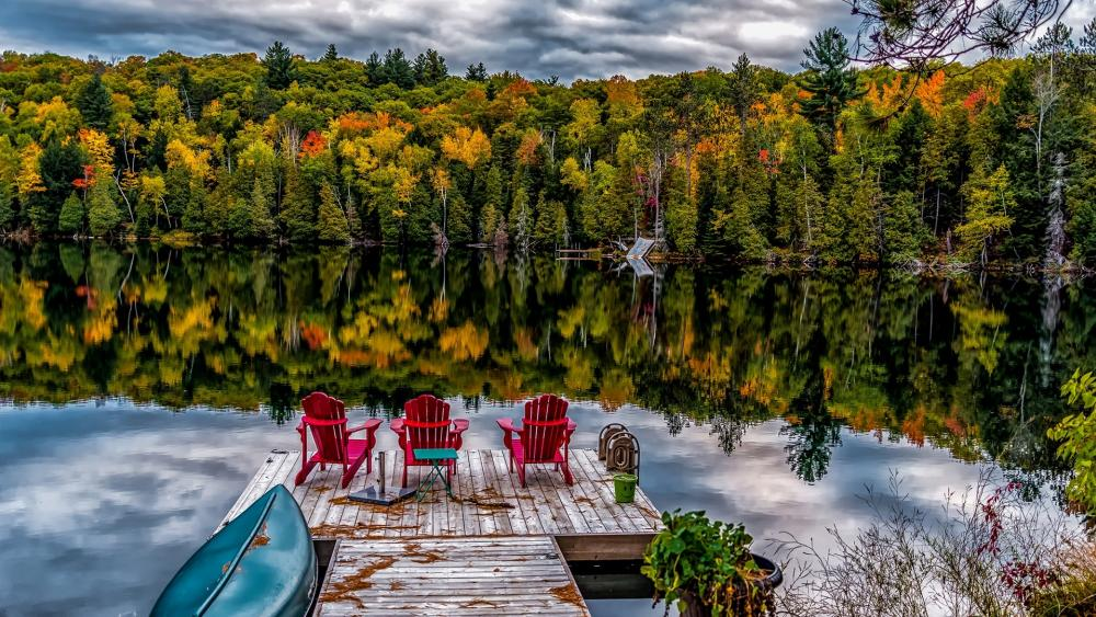 Jetty with seats on a calm lake at fall wallpaper