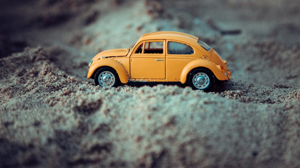 Volkswagen Beetle toy car in the sand wallpaper