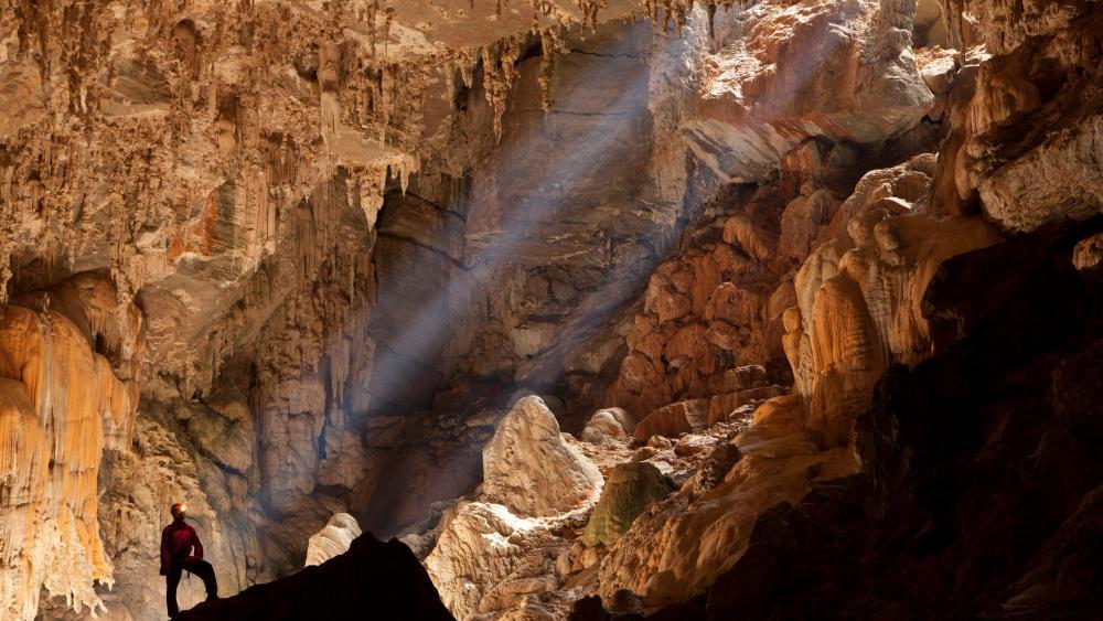 Speleologist Observing Sun Rays Inside the Terra Ronca Cave wallpaper