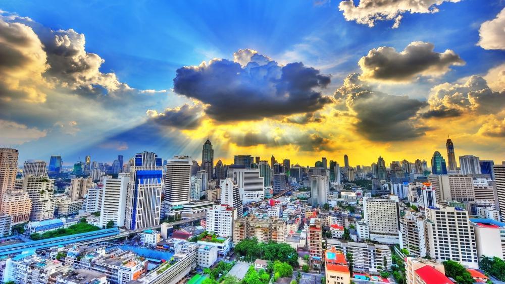 Rays of sunlight bursting through clouds above Bangkok City wallpaper