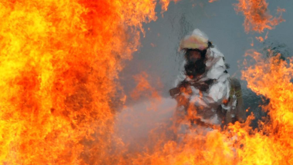 U.S. Air Force Firefighter Sprays Water on a Fire wallpaper