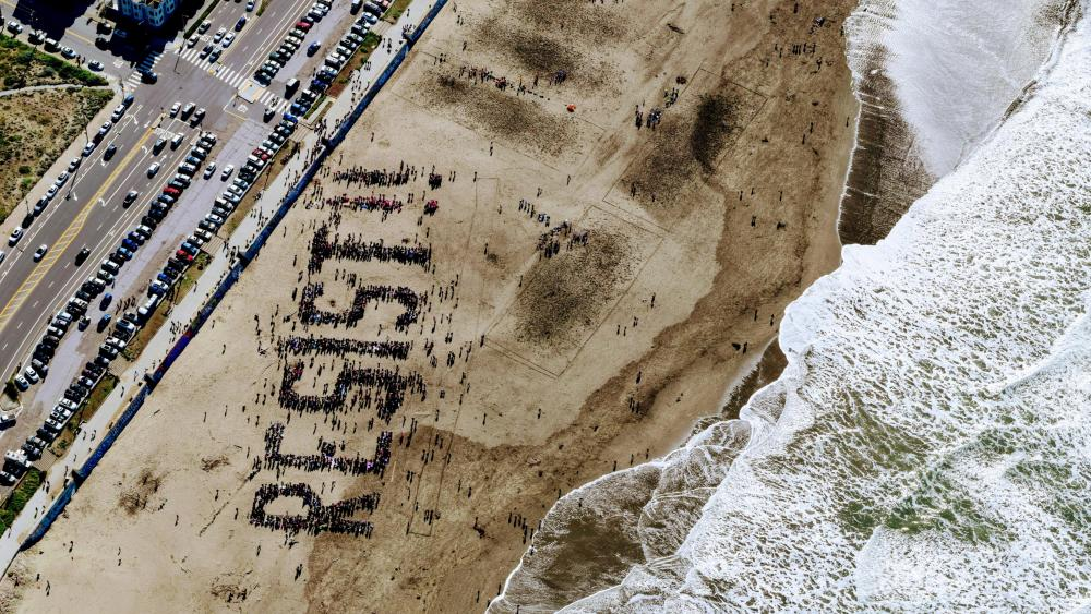 Drone View of Resist Protest on the Sand of Ocean Beach wallpaper
