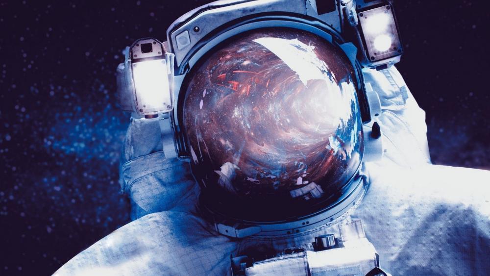 Astronaut with space reflected in helmet wallpaper