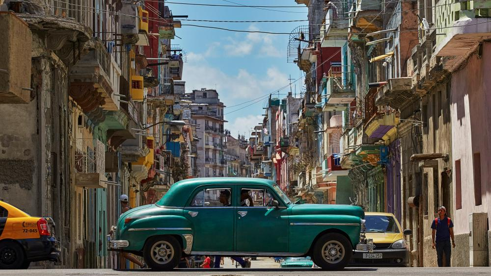 Oldtimer crossing one of Havana main streets wallpaper
