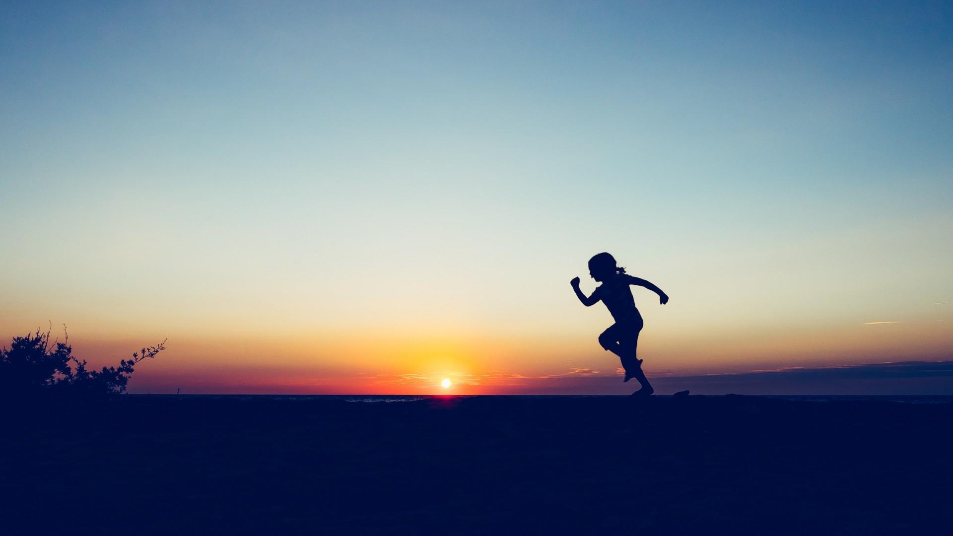 Jumping girl silhouette in the sunset wallpaper