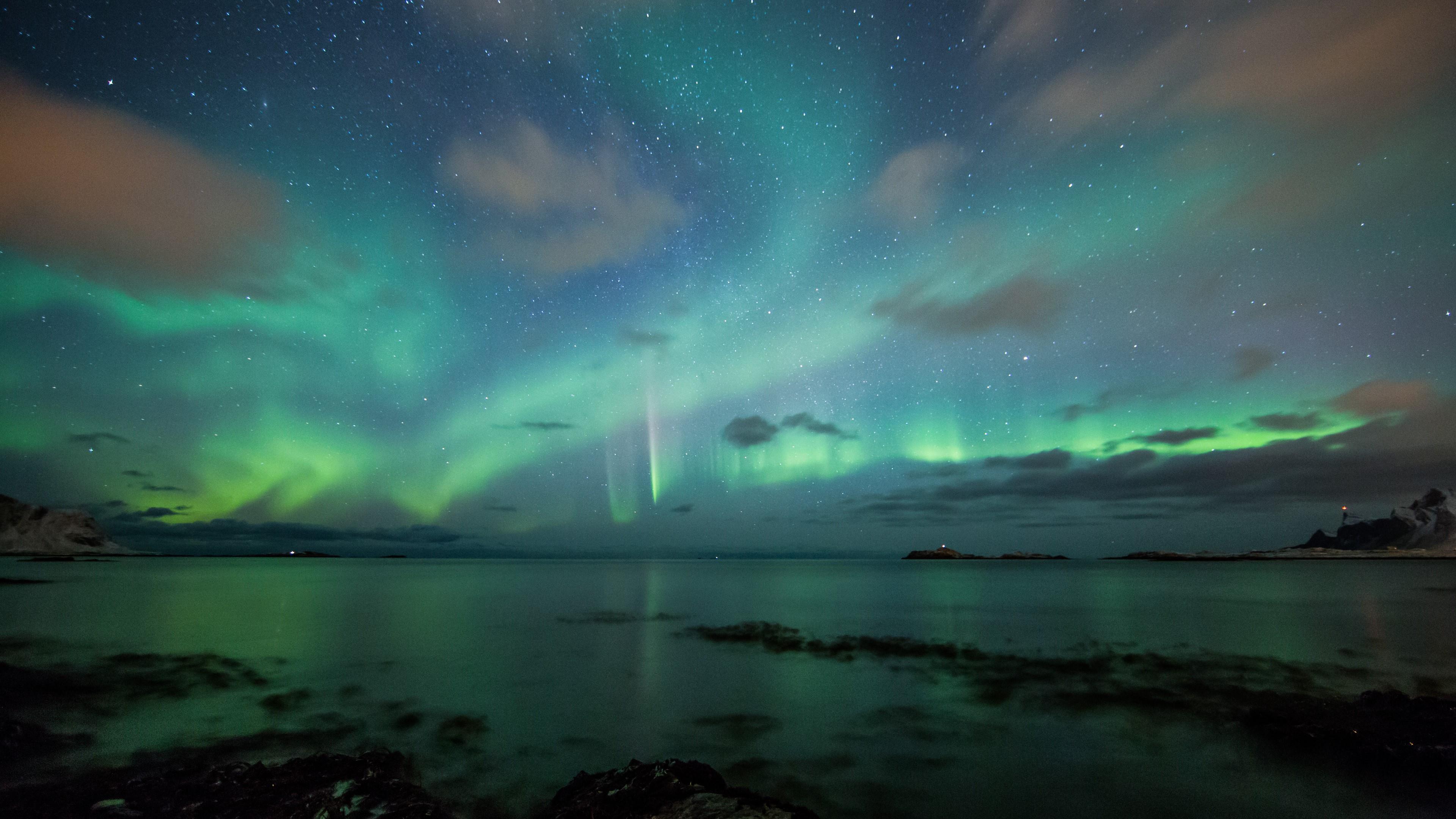Green aurora borealis on the starry night sky wallpaper