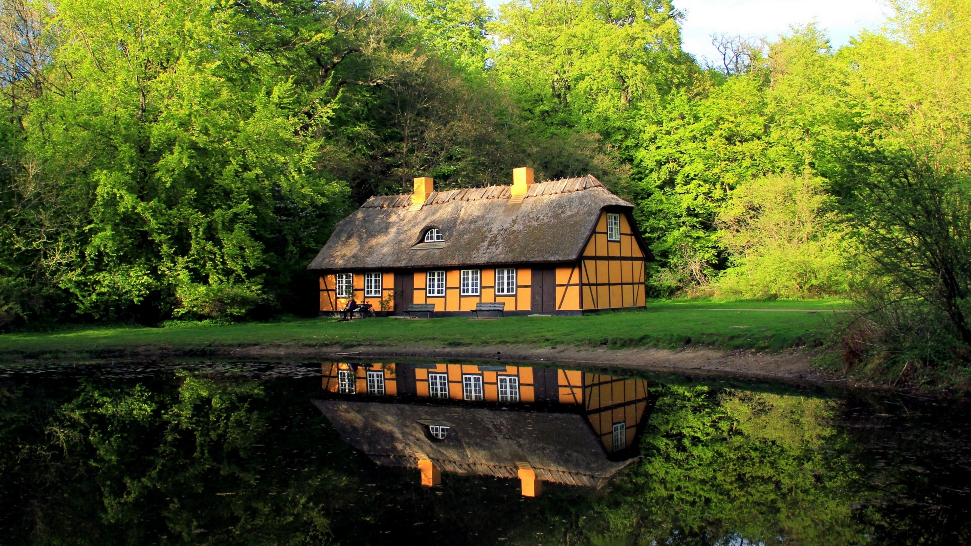 Cozy house next to a pond wallpaper