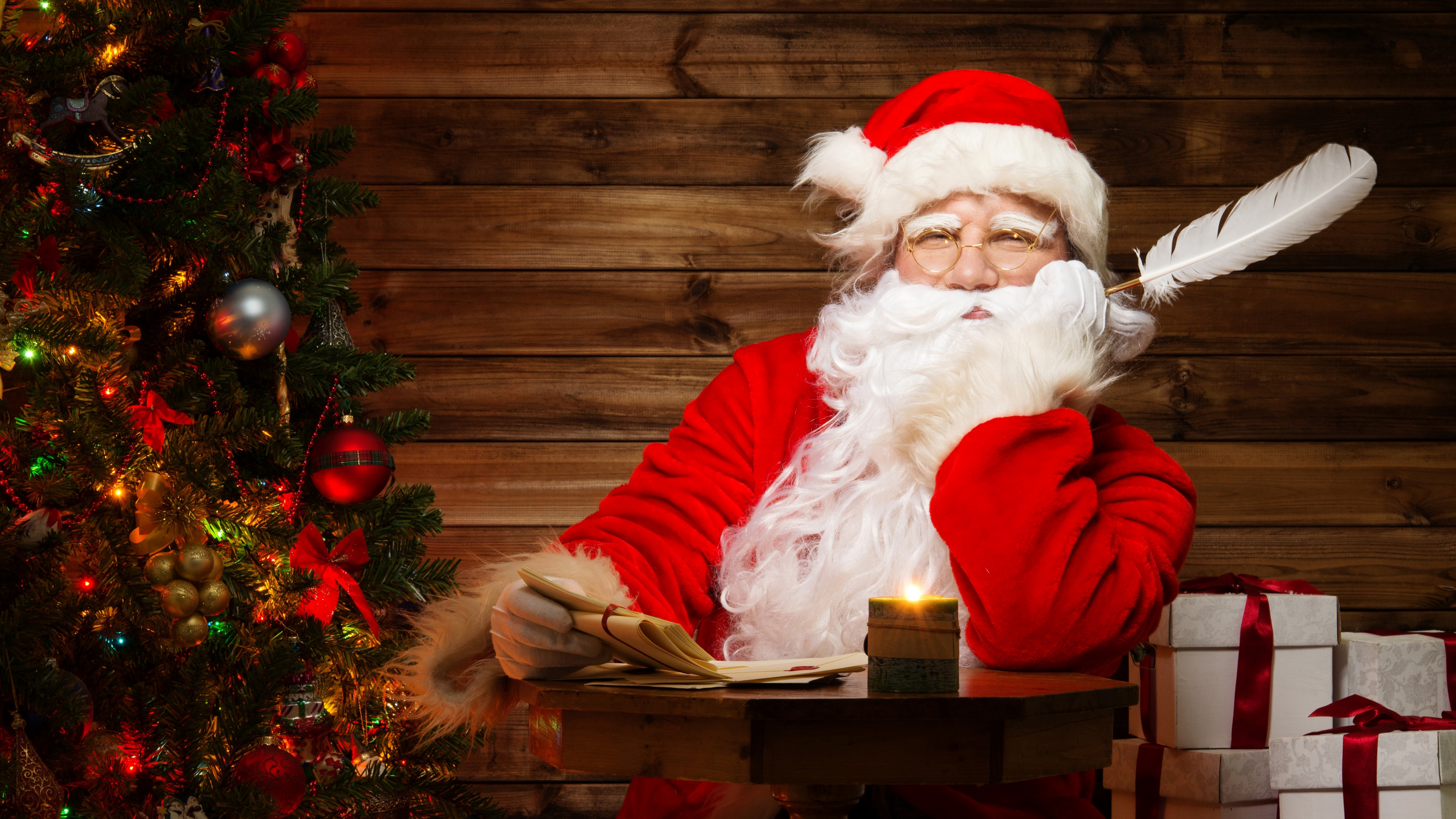 Santa Claus with gifts in his log cabin wallpaper