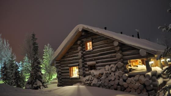 Snowy log cabin at night wallpaper