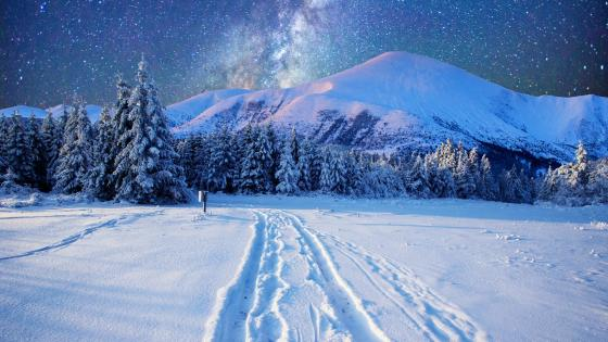 Milky way on the night sky over the snowy mountains wallpaper