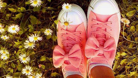 Tennis shoes on daisy lawn wallpaper