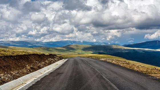 Cloudy sky above the endless road wallpaper