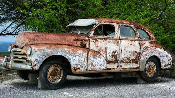 Broken rusty vintage car on bricks wallpaper