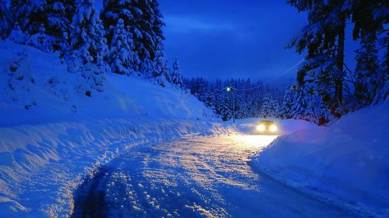 Car headlights in snowy night wallpaper