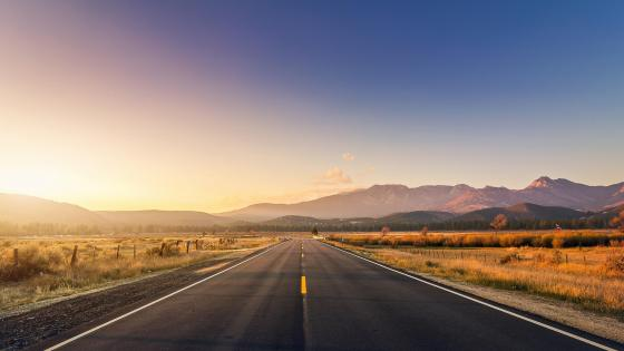 Road with sunset and mountains wallpaper