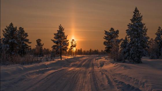 Sunset shining on the winter road wallpaper