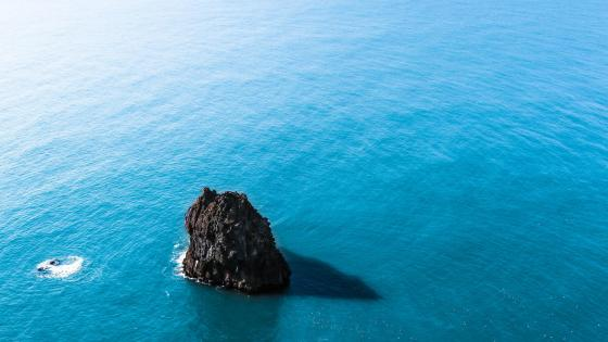 Small rock islet in the blue sea wallpaper