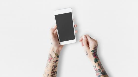 Tattooed arms with a white cell phone wallpaper