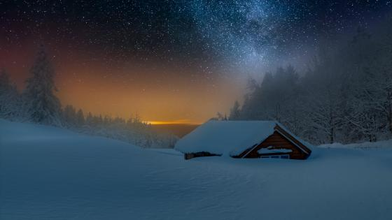 Snowy log cabin under the Milky Way wallpaper