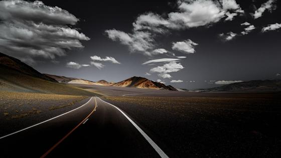 Endless road with fluffy clouds wallpaper