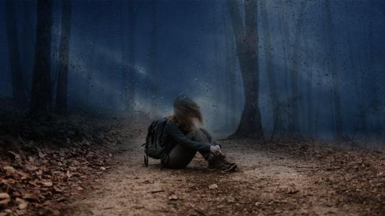 Lone girl in the dark stormy forest wallpaper