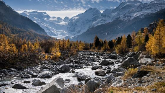 Rocky creek surrounded by snowy mountains wallpaper
