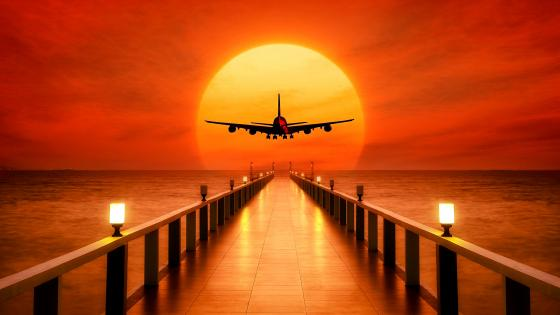 Airplane over the pier in the sunset wallpaper