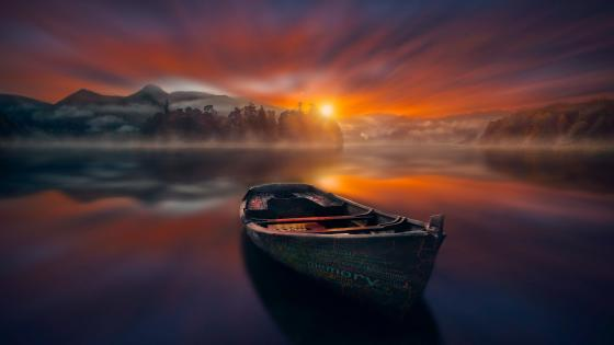 Calm lake with a boat at sunset wallpaper
