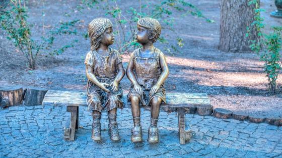 Bronze kids on bench statue wallpaper