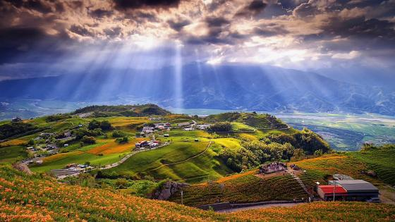 Beautiful landscape with sunbeams in the clouds wallpaper