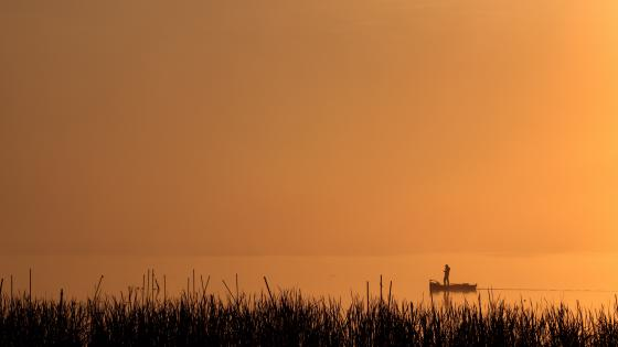 Boat silhouette on a lake at sunset wallpaper
