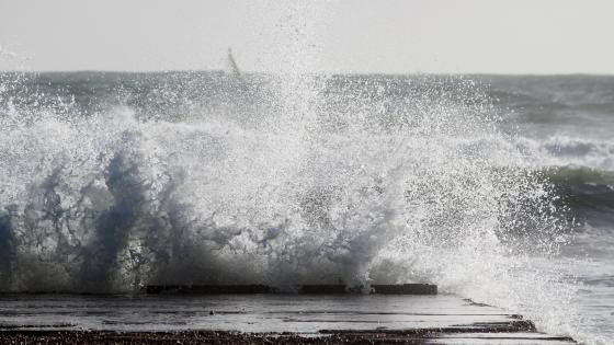 Sea waves hitting brown wooden dock wallpaper