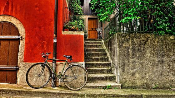 Bicycle resting on the wall of the house wallpaper
