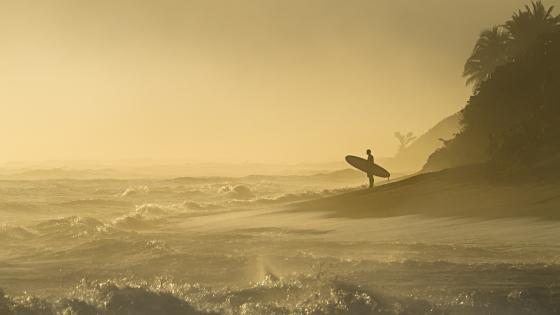 Surfes with surfboard and the surging sea wallpaper