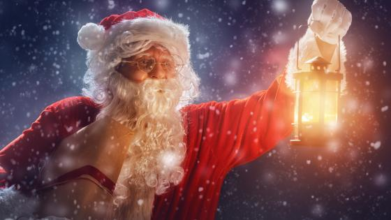 Santa Claus with a lantern in the snowfall wallpaper