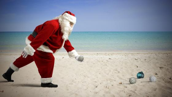 Santa playing on the sandy beach wallpaper