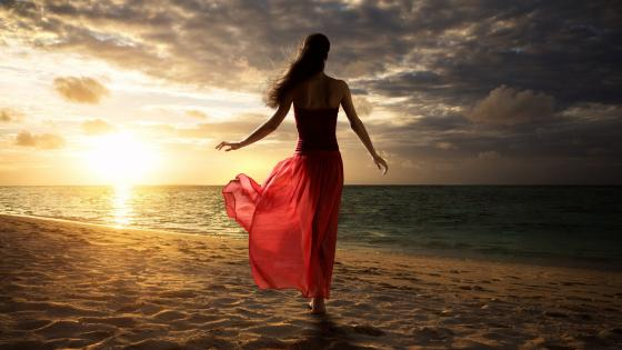 Woman in red dress on the beach wallpaper